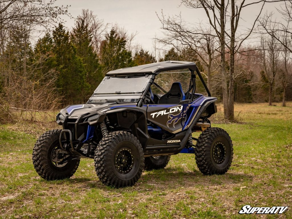 A Honda Talon 1000X with a flip windshield, roof, lift kit, and Warrior tires.
