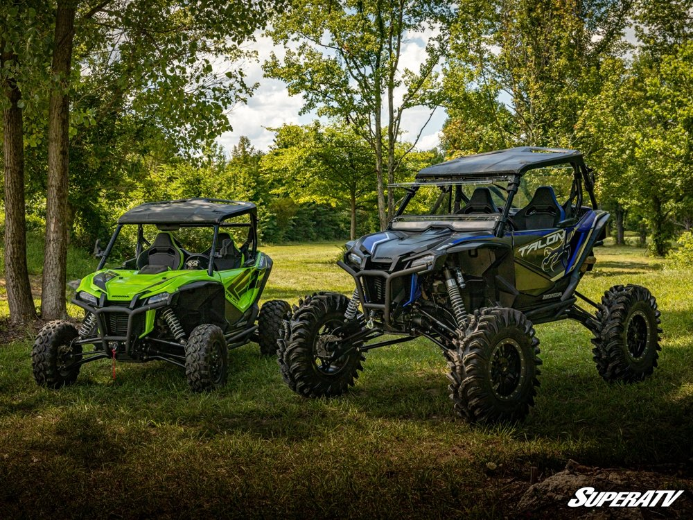A Honda 1000X with a big lift kit standing next to a stock Honda Talon 1000R. UTV tire size is greatly increased on the lift vehicle.