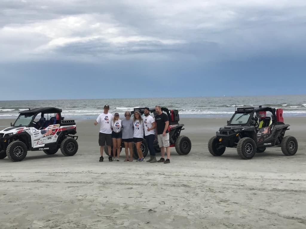 Nitro Circus' Hubert Rowland and his friends stand in front of the three Polaris machines they used to ride the entire length of the TransAmerica Trail.