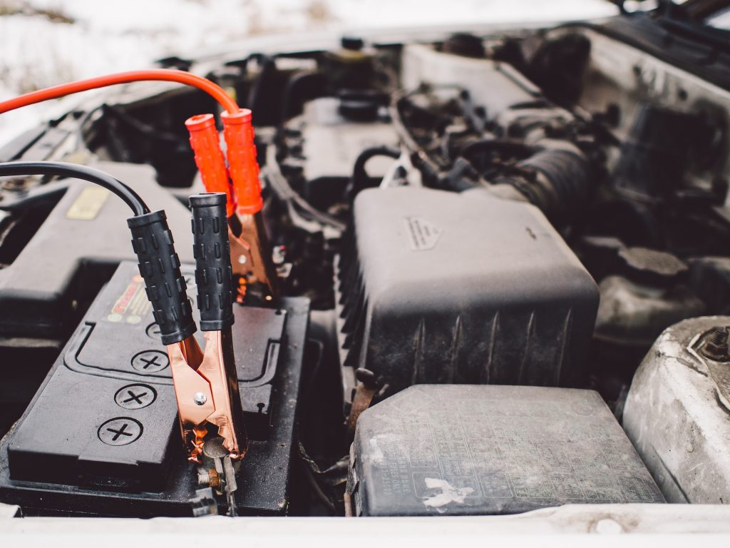 A pair of jumper cables attached to a vehicle battery