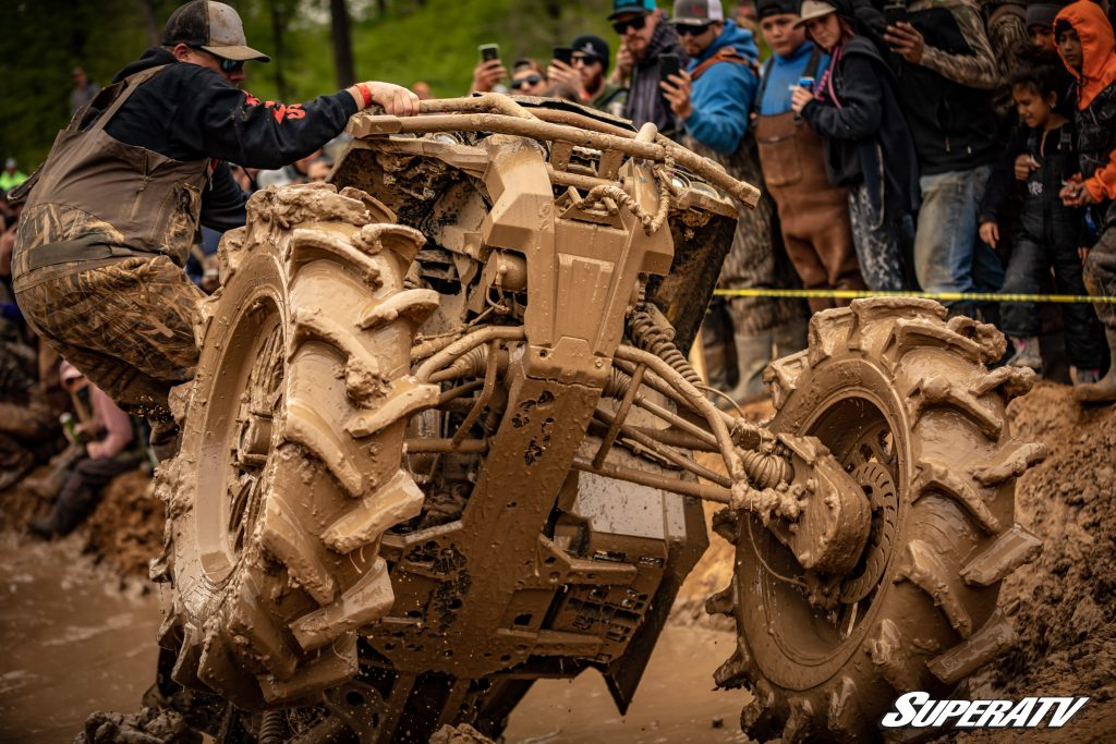 An ATV is completely covered in mud at an off-roading event.