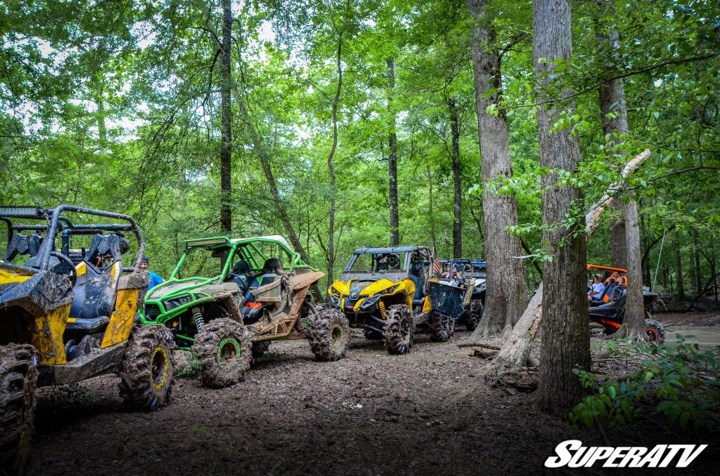 A line of UTVs on a trail at Muddy Bottoms