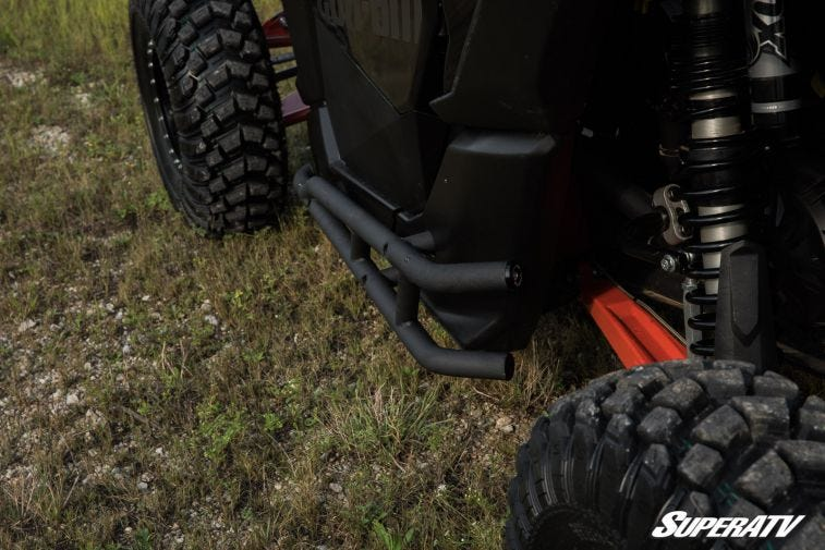 A close-up shot of black nerf bars installed on a machine, protecting the plastic frame of the vehicle.