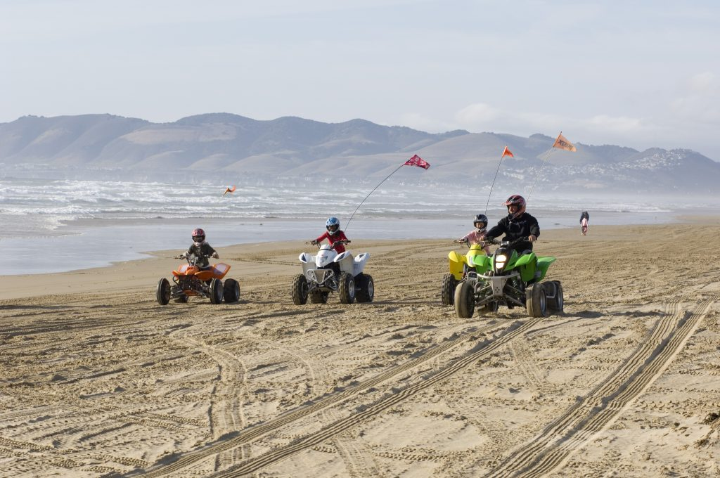 A father and three children ride ATVs on the beach