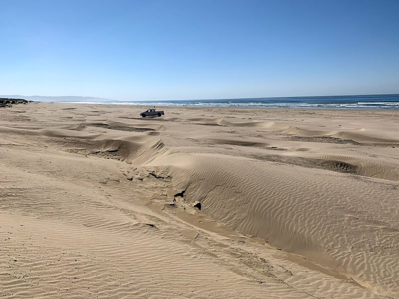 Oceano dunes, the pacific ocean, and a truck parked on the beach.