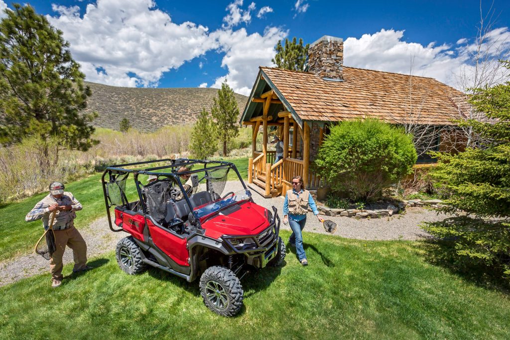 A Honda Pioneer parked in front of a cabin