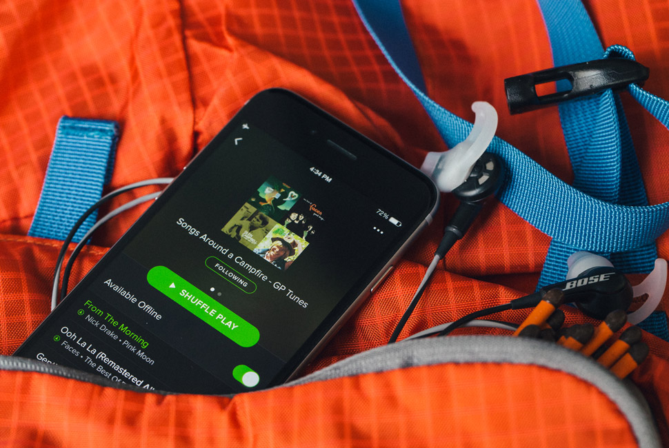 An iPhone is open to an outdoors playlist.