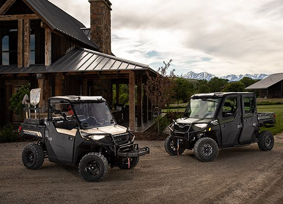 Two new Polaris machines are parked outside of a house