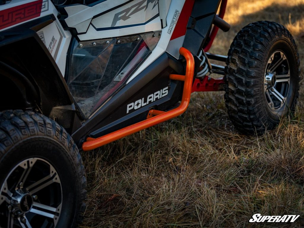 This close-up shows a set of orange nerf bars installed on a RZR.