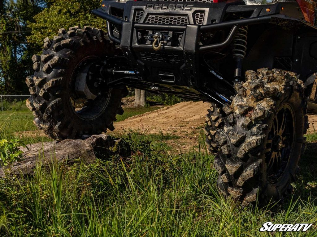 A Polaris Ranger taking advantage of a wide suspension to roll over obstacles easily.