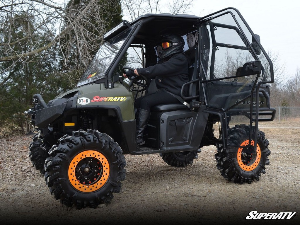 A Polaris Ranger is closed in with a front windshield, rear windshield, doors, and a roof.