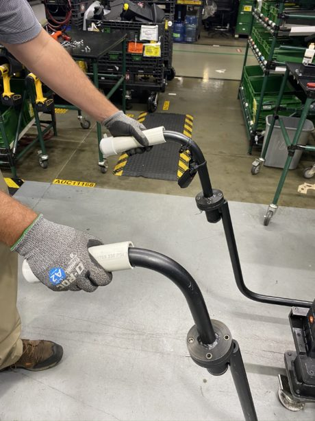 A Honda employee demonstrates how to use the Personal Use Safety Handles, a device invented by employee Jason Sherron to curb the spread of germs while working on the floor.