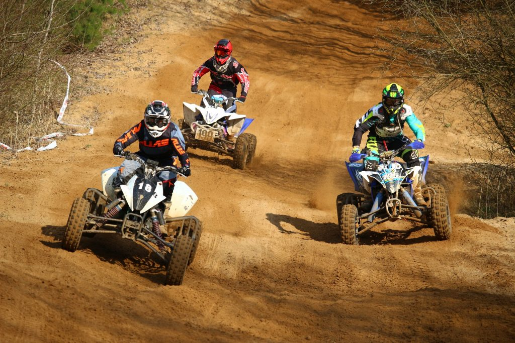three quads racing on a track