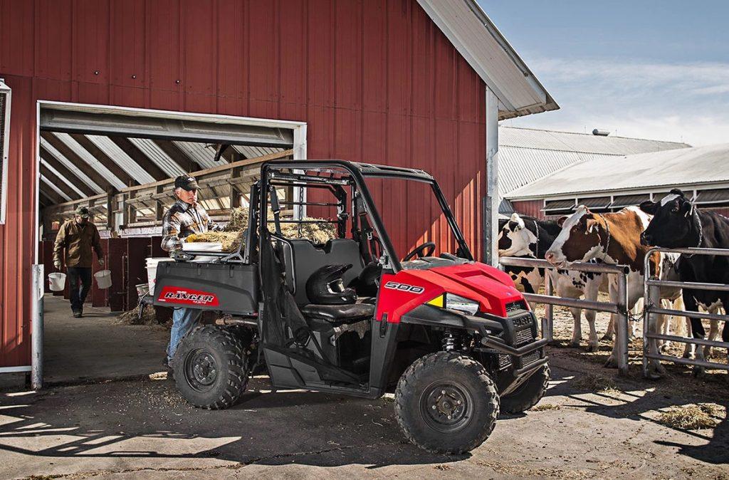 A Polaris Ranger 500 next to a red barn