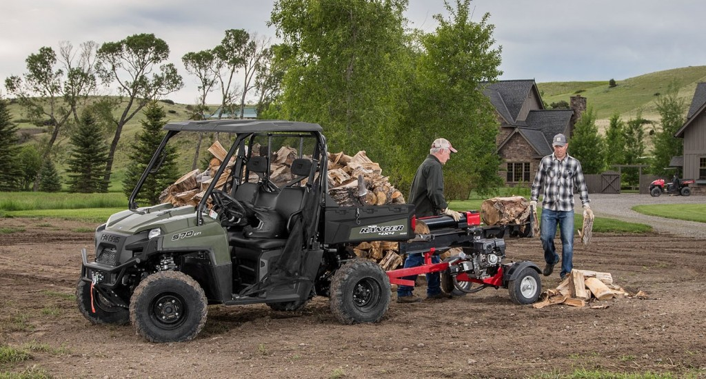 This photo shows two men chopping wood and loading it into the bed of a Polaris Ranger.