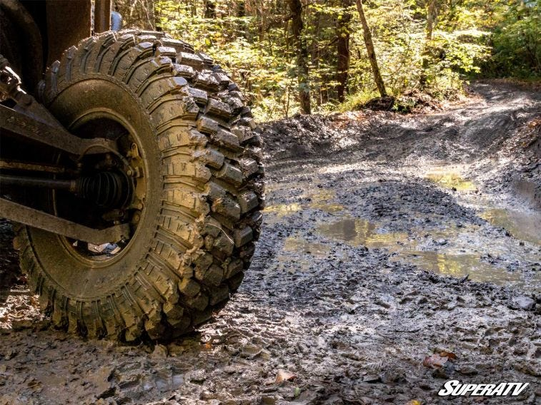 This close-up photo shows a SuperATV RT warrior tire on a muddy trail.