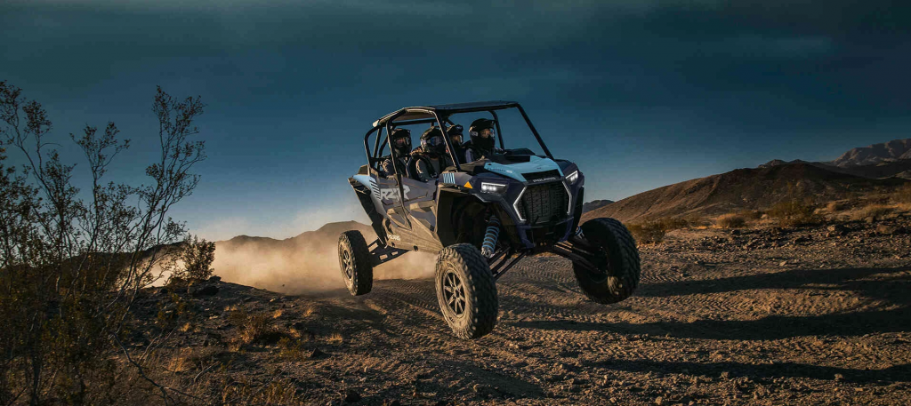 A full family in a Polaris RZR XP 4 Turbo S hitting high speed.