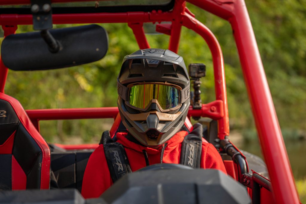 A UTV driver wearing goggles, a helmet, and a safety harness