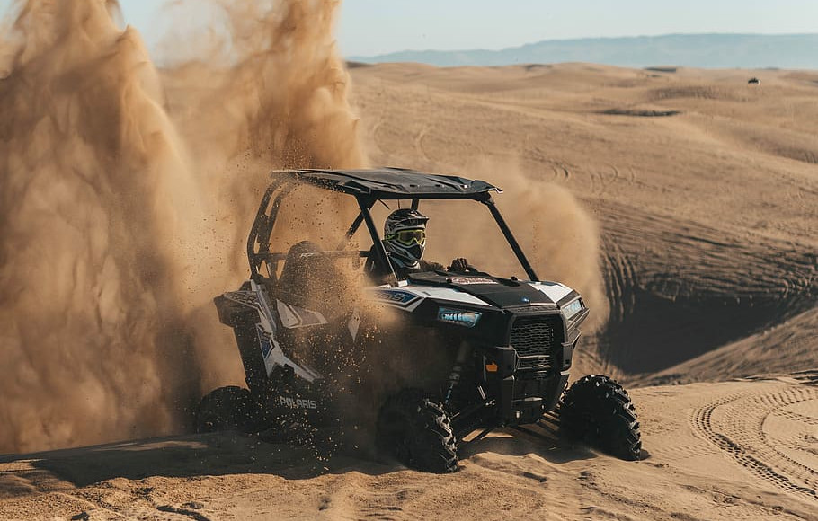 A UTV kicks up some sand in the dunes