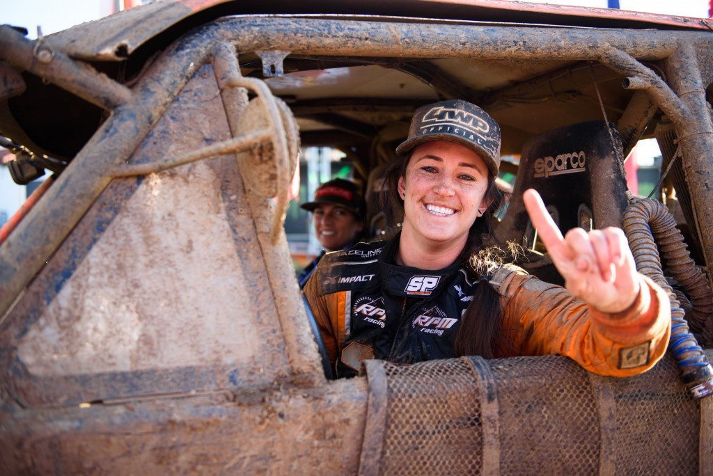 Sara Price smiles from the driver's seat of her race truck and holds up one finger after winning the SCORE International Trophy Truck Spec Championship in 2019.