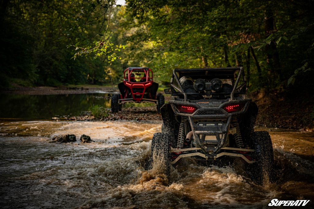 Two side-by-sides drive down a creek in the woods
