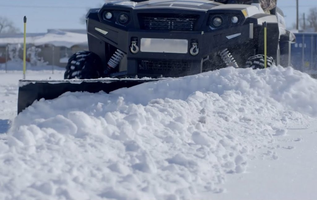 A snow plow on a UTV pushing large amounts of snow