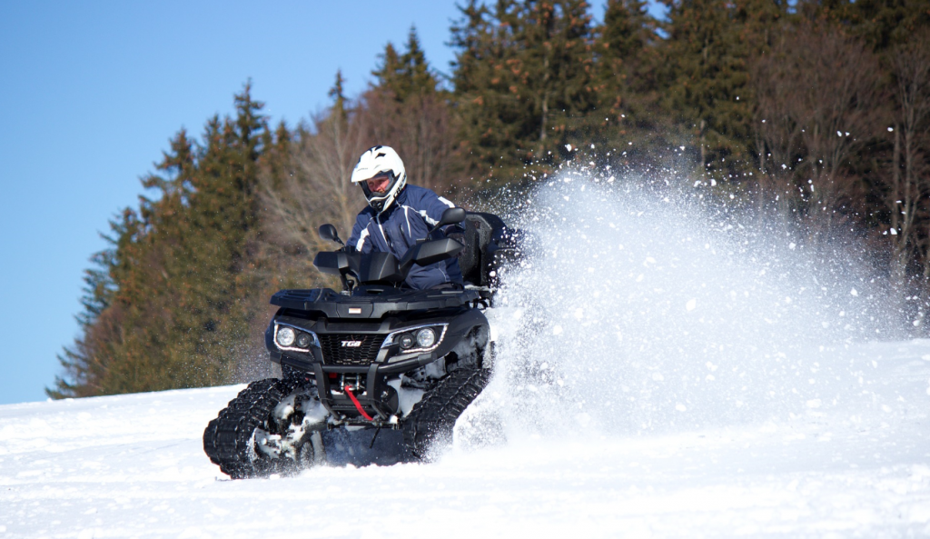 An ATV with snow tracks installed navigates snow and ice easily.