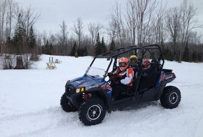 Shawn King riding a UTV through the snow with his family
