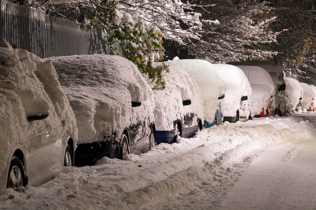 Cars covered in snow parked on a very snowy street