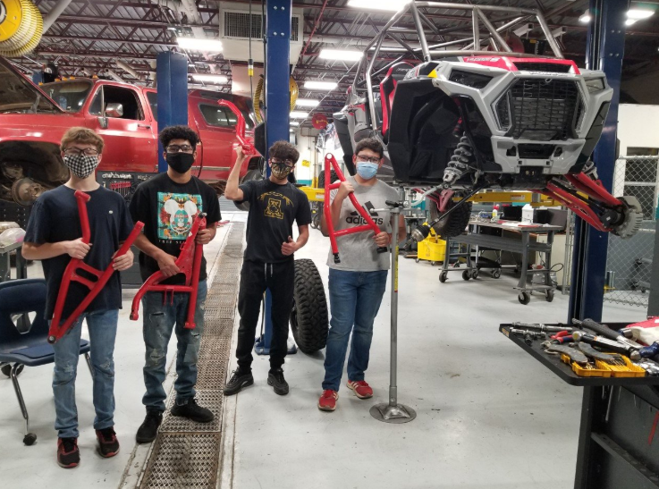 Steven Gonzalez's students holding the A-arms they installed on his Polaris RZR
