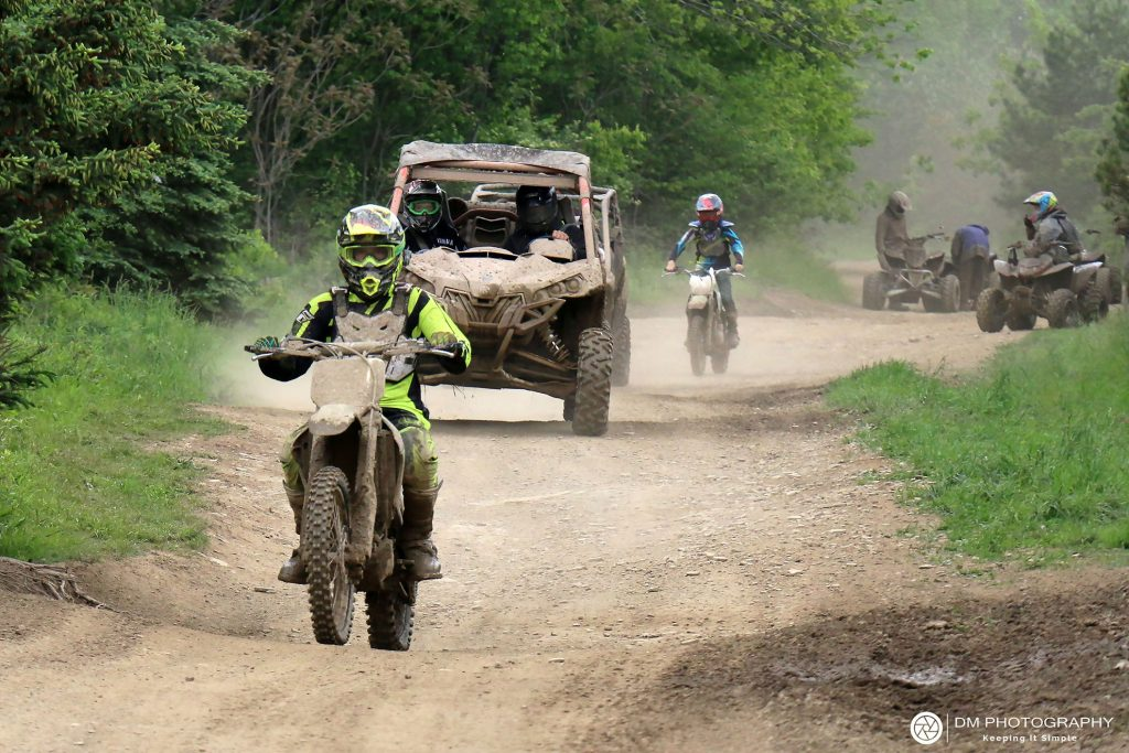 Dirt bikes, side-by-sides, and ATVs ride down a trail at Tall Pines ATV Park