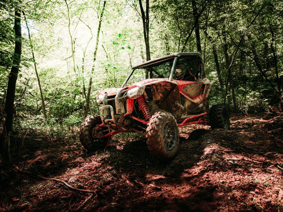 A Honda Talon 1000R on a rough wooded trail