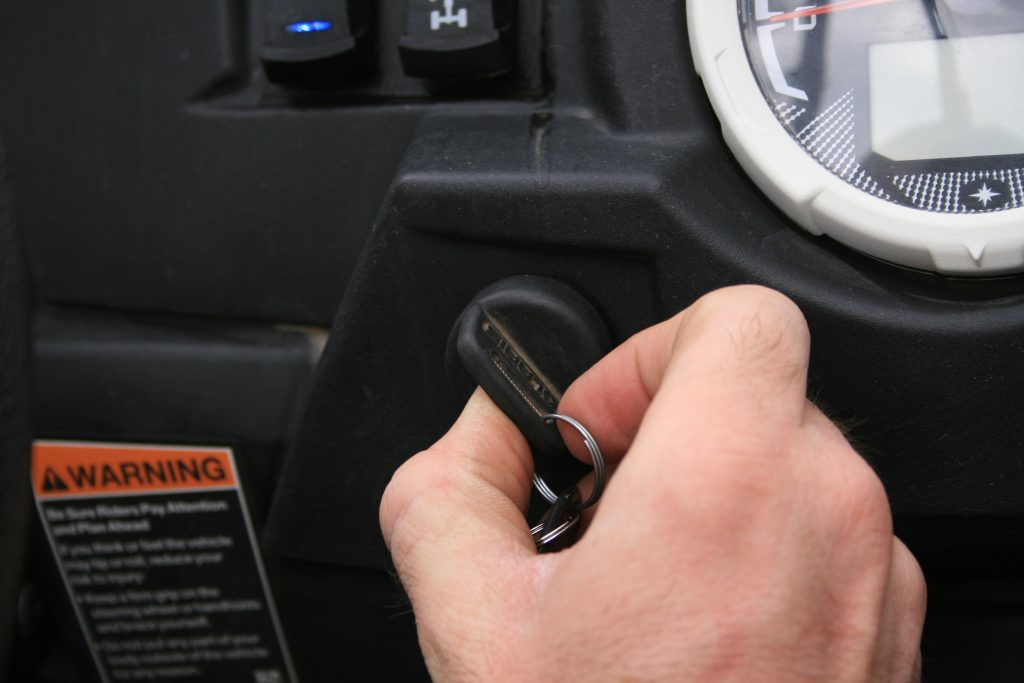 This photo shows someone turning the key in the ignition of a UTV.