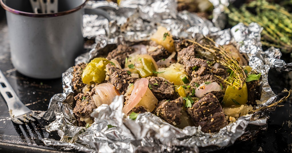 This is an up-close shot of meat, potatoes, and vegetables wrapped up in aluminum foil—otherwise known as a hobo dinner. This is the most easy way to prep delicious meals ahead of time that you can enjoy on the trails.