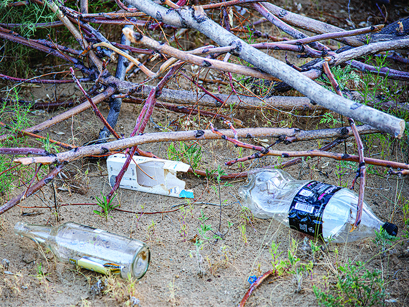 Empty bottles and other debris litter an off-road trail