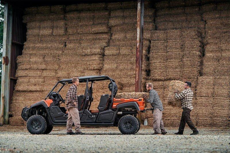 Three men loading bales of hay into a Yamaha Viking VI