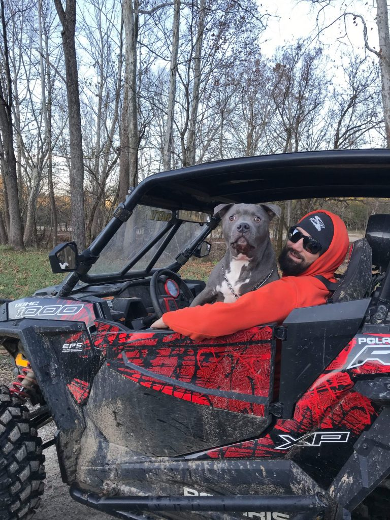 Wilber sits on the lap of SuperATV's social media guy, Corey, behind the wheel of their RZR.