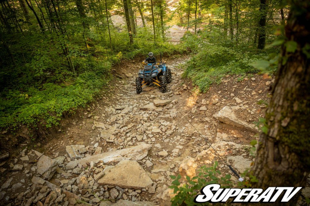 A rider winches an ATV up a hilly trail using a tree