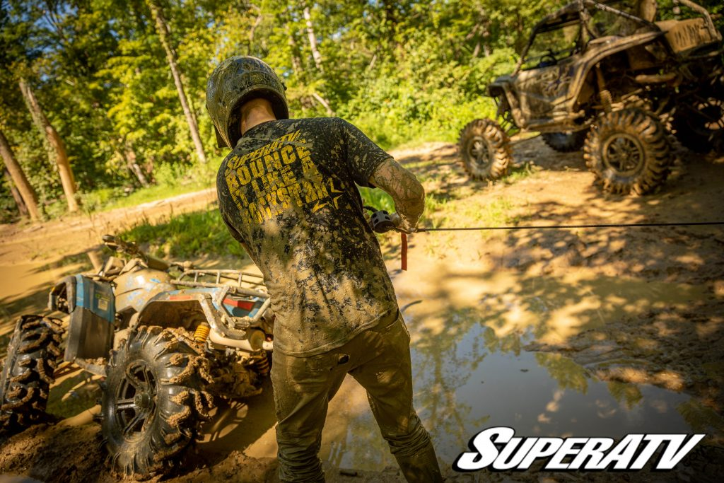 A man handles synthetic winch rope to pull out an ATV stuck in mud.