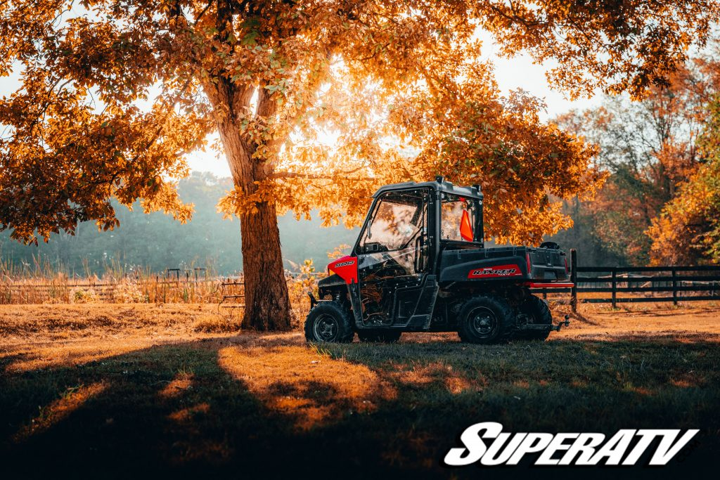 A Polaris Ranger getting filled up with branches in a field.