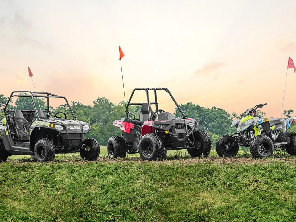 Youth ATVs and UTVs parked in a row